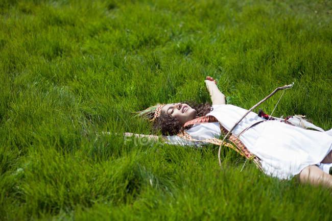 Девушка в костюме лежала в траве — стоковое фото