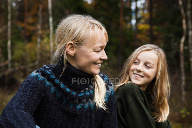 Улыбающиеся мать и дочь в лесу — стоковое фото