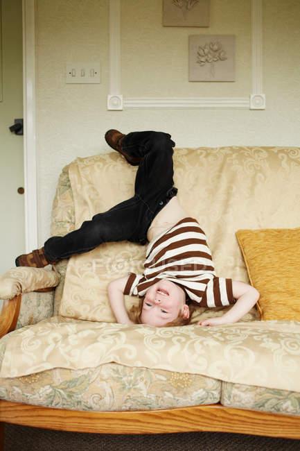 Niño jugando en sala de estar sofá - foto de stock