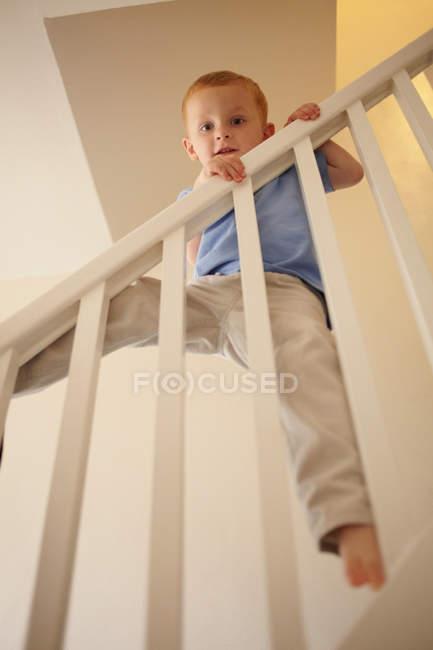 Boy climbing banister of steps — Stock Photo