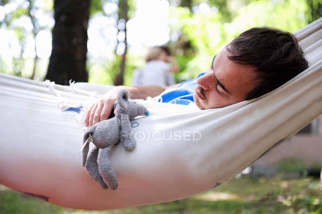 Mann schläft in Hängematte mit Spielzeug — Stockfoto