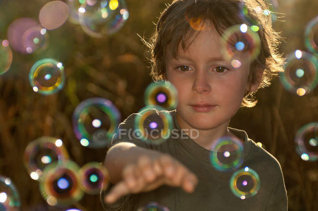 Boy playing with bubbles outdoors — Stock Photo