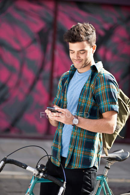 Young man on bicycle reading text — Stock Photo