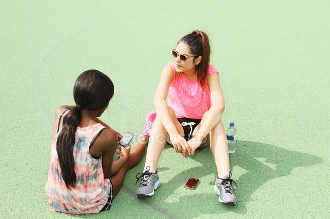 Women sitting on basketball court — Stock Photo