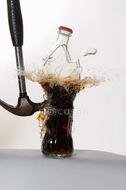 Молоток разбивающий стеклянную бутылку соды — стоковое фото
