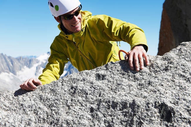 Man climbing on rock and looking aside — Stock Photo