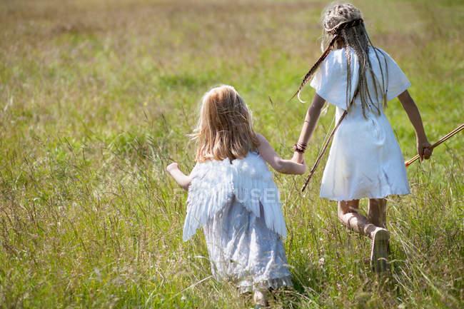 Chicas en trajes caminando en el campo - foto de stock