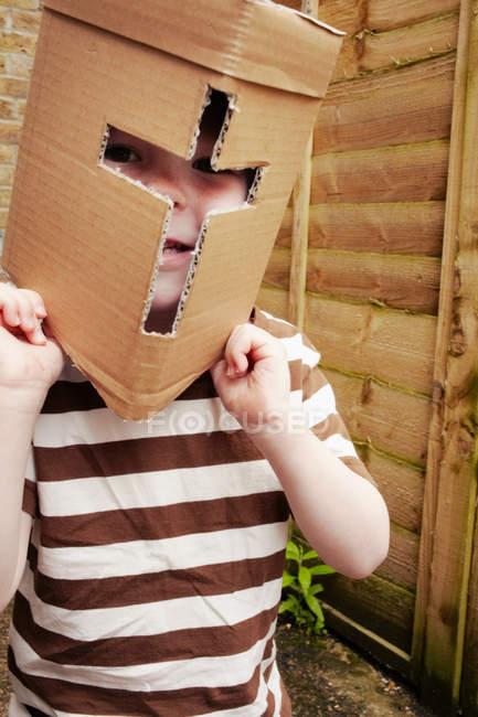 Boy wearing cardboard helmet — Stock Photo