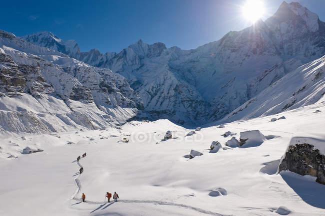 Excursionistas en paisaje de montaña nevado - foto de stock