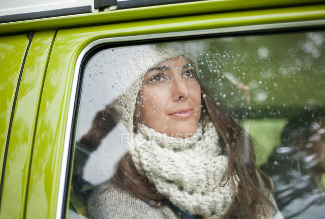 Woman looking out rainy window — Stock Photo