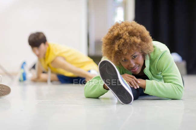 Two dancers stretching in studio — Stock Photo