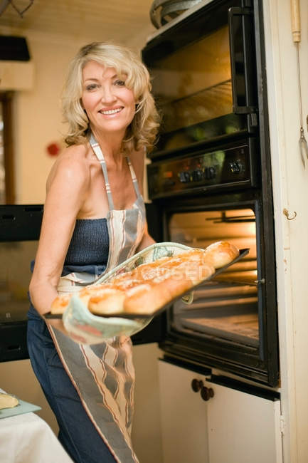 Woman holding bakery in kitchen — Stock Photo