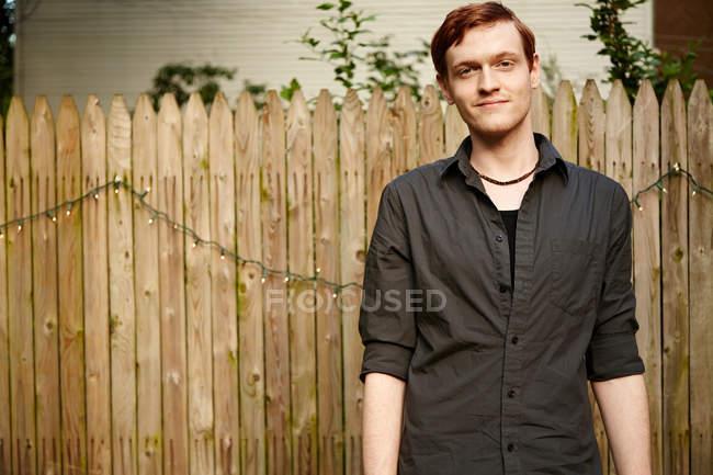 Mann steht vor Gartenzaun — Stockfoto