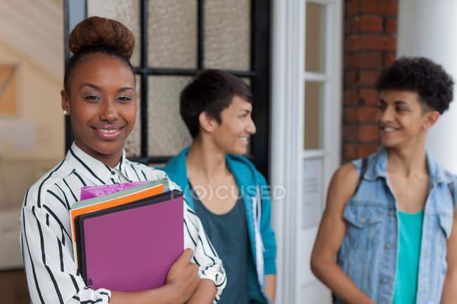 Studente sorridente che tiene cartelle — Foto stock
