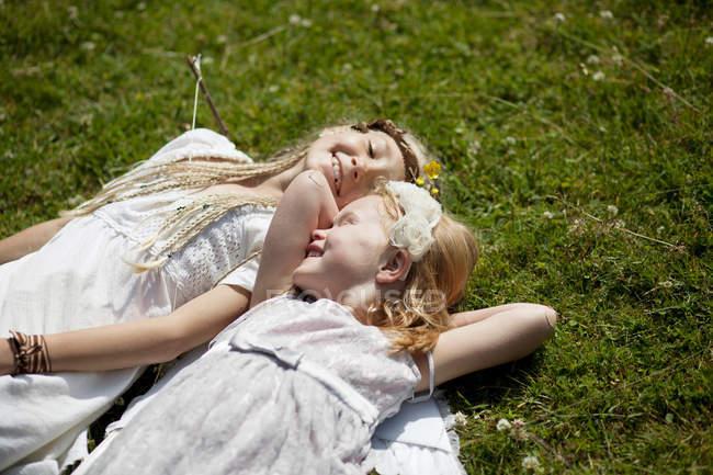 Девушки в костюмах, лежащие в траве — стоковое фото