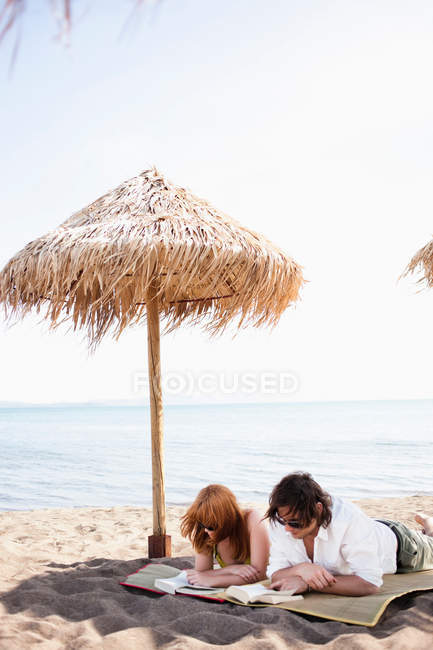 Пара читання під парасолька від сонця — стокове фото