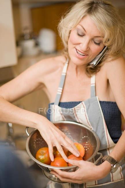 Mujer cocinando y usando teléfono - foto de stock