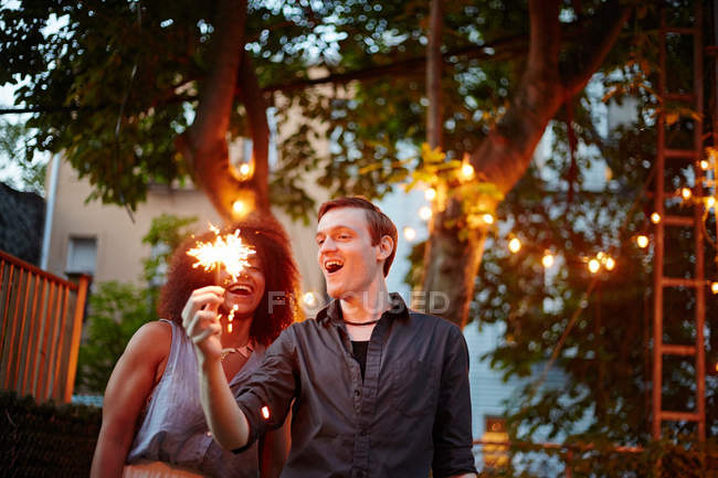 Jovem homem segurando sparkler — Fotografia de Stock