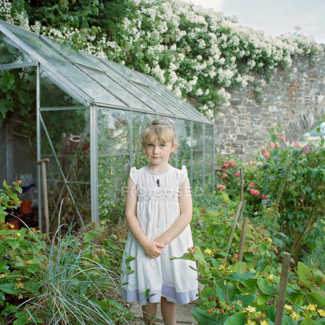 Little girl standing by greenhouse — Stock Photo