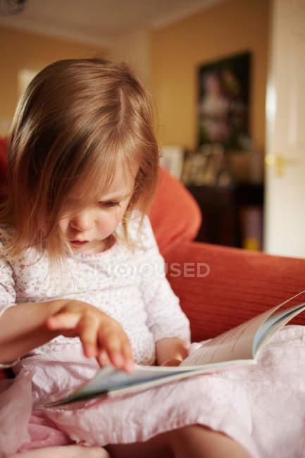 Ragazza lettura libro in poltrona — Foto stock