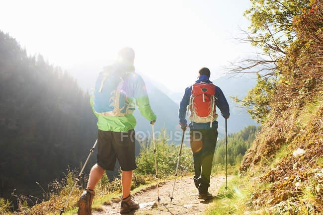 Dos hombres caminando en las montañas - foto de stock