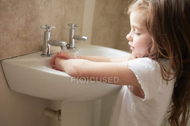 Girl washing hands in bathroom — Stock Photo