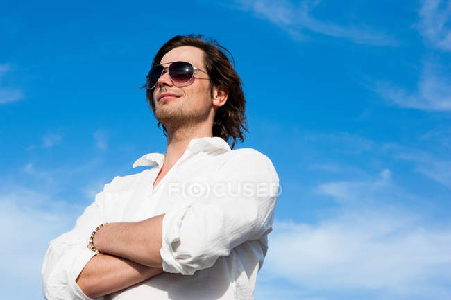 Young man in front of blue sky — Stock Photo