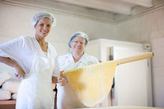 Trainee with chef holding rolling pin — Stock Photo