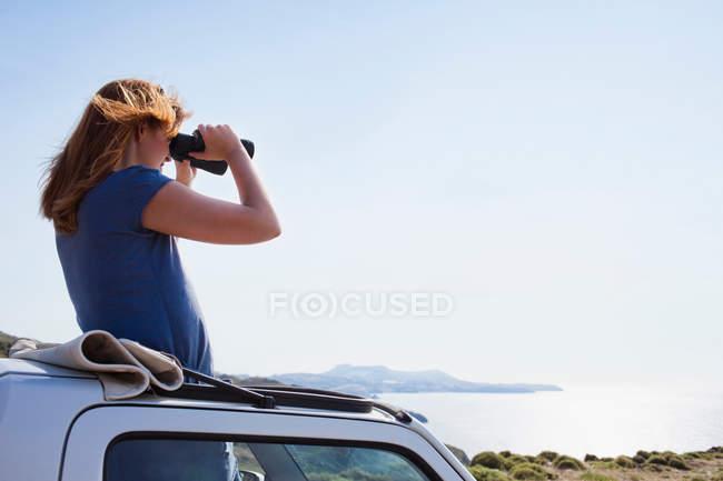 Mujer mirando a través de prismáticos - foto de stock