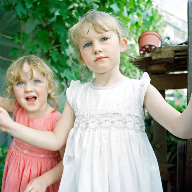 Two little girls in greenhouse — Stock Photo