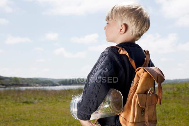 Мальчик, несущий банку в травянистом поле — стоковое фото