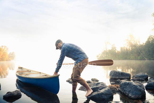 Man pushing canoe — Stock Photo
