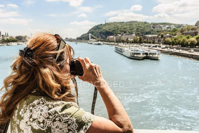 Женщина фотографирует реку — стоковое фото