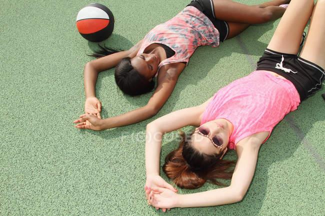 Женщины, лежа на баскетбольную площадку — стоковое фото
