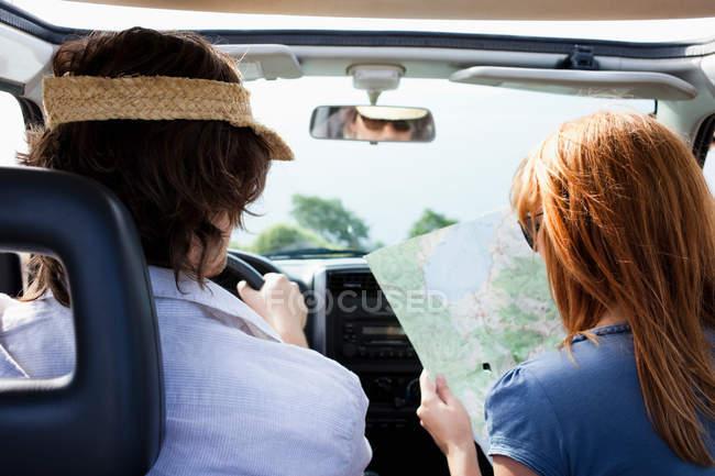 Пара в автомобіль, дивлячись на карту — стокове фото