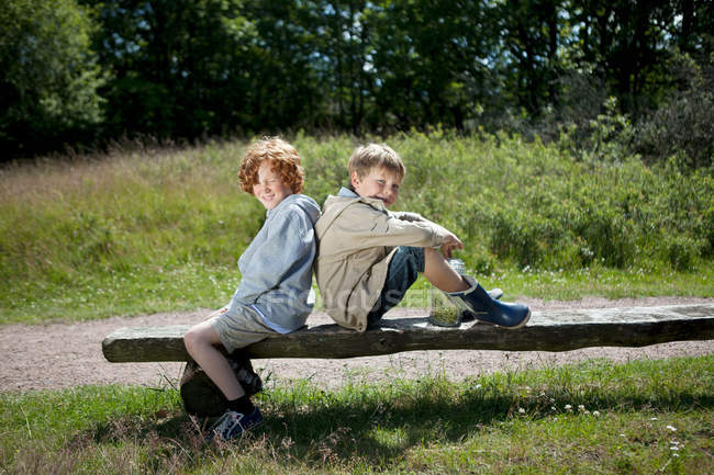 Zwei Jungen sitzen auf Holzbank — Stockfoto