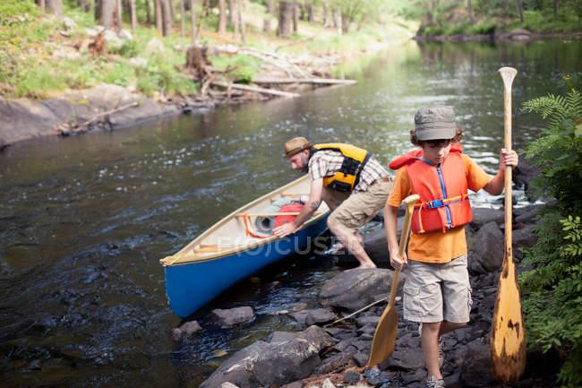 Vater und Sohn schieben Kanu — Stockfoto