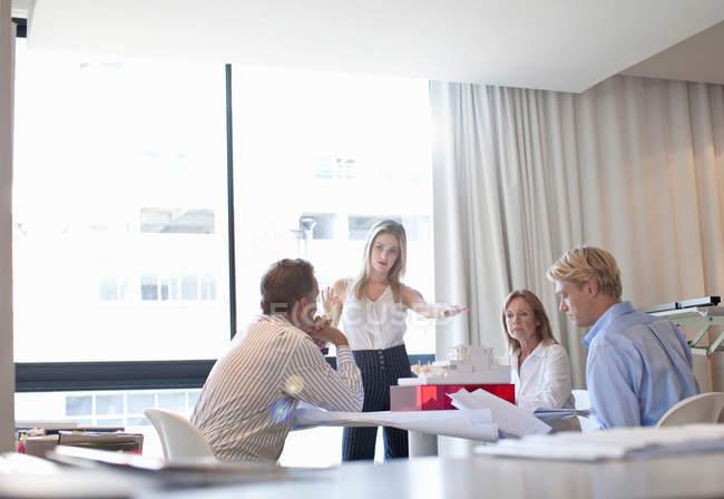 Menschen diskutieren Modell im Amt — Stockfoto