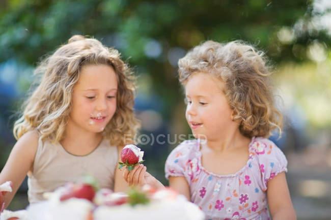 Girls eating strawberries outdoors — Stock Photo