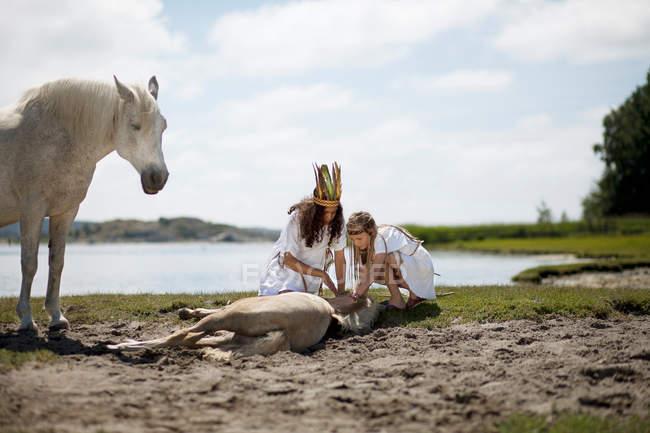 Ragazze petting cavallo sulla spiaggia di sabbia — Foto stock