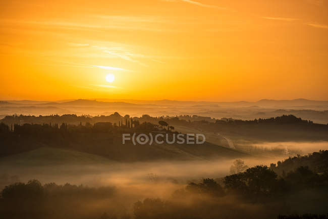 Sunrise over foggy rural landscape — Stock Photo