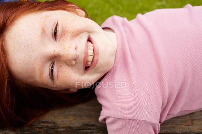 Lächelndes Mädchen, das auf Holzklotz liegt — Stockfoto