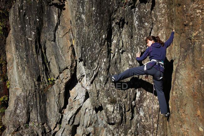 Женщина карабкается по скале — стоковое фото