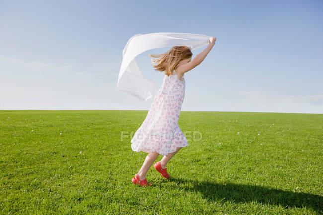 Девушка бегает с белым шарфом — стоковое фото