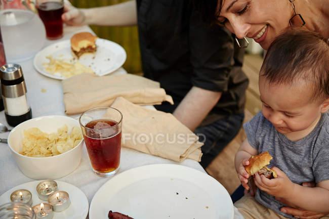 Mère, tenant le petit garçon à table — Photo de stock