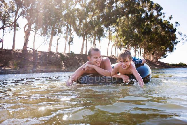 Homem e menino flutuando no anel inflável — Fotografia de Stock