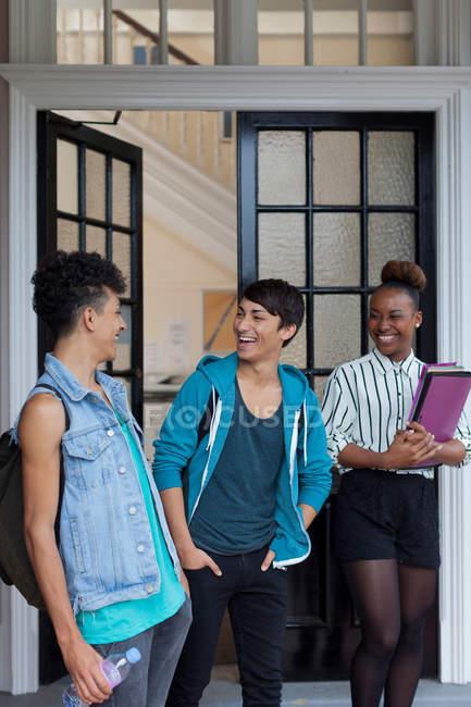Tre studenti sorridenti nel campus — Foto stock