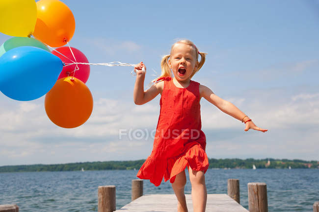 Девушка держит шары на деревянном пирсе — стоковое фото