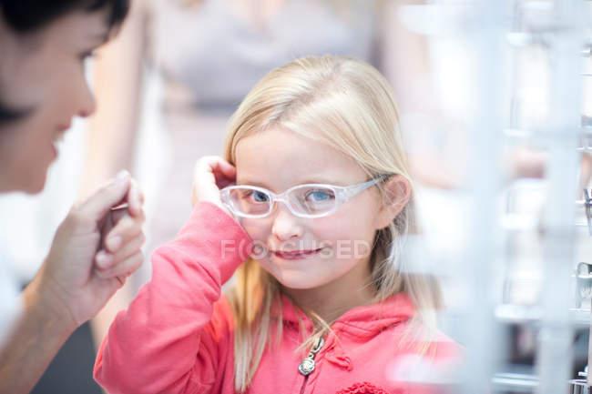 Giovane ragazza cercando su occhiali da vista — Foto stock