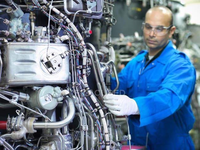 Engenheiro aeronáutico inspecionando motores a jato em armazenamento — Fotografia de Stock